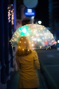 Rear View Of Woman Standing Under Illuminated Umbrella On Footpath At Nightの写真素材 [FYI04478961]
