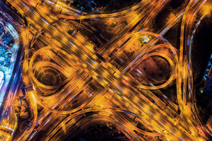Aerial View Of Light Trails On Bridge In City At Nightの写真素材 [FYI04479128]