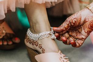 Cropped Hand Of Bridesmaid Adjusting Bride Ankletの写真素材 [FYI04479509]