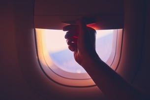 Cropped Hand Of Person By Airplane Windowの写真素材 [FYI04479537]