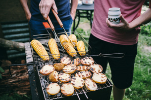 Midsection Of Men Preparing Food On Barbecue Grillの写真素材 [FYI04479729]