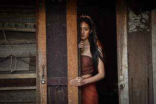 Portrait Of Young Woman Standing By Wooden Doorの写真素材 [FYI04479804]