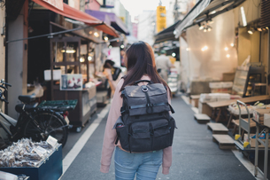 Rear View Of Woman With Backpack Standing On Street In Cityの写真素材 [FYI04479851]