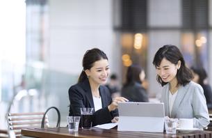 テラスで打ち合わせをする2人のビジネス女性の写真素材 [FYI04479917]