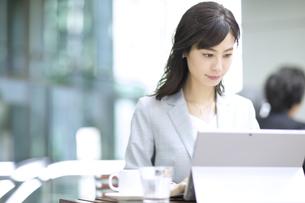 テラスでパソコンを操作するビジネス女性の写真素材 [FYI04479918]