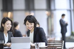 テラスで打ち合わせをする2人のビジネス女性の写真素材 [FYI04479919]