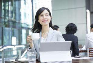 テラスでパソコンの前でくつろぐビジネス女性の写真素材 [FYI04479920]