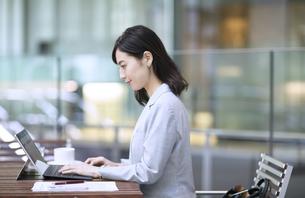 テラスでパソコンを操作するビジネス女性の写真素材 [FYI04479922]