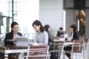 テラスで打ち合わせをする2人のビジネス女性の写真素材 [FYI04479923]
