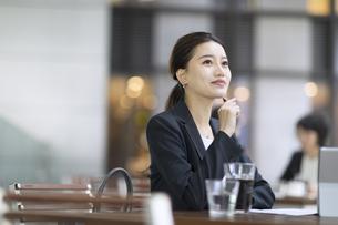 テラスで遠くを見て考えるビジネス女性の写真素材 [FYI04479927]