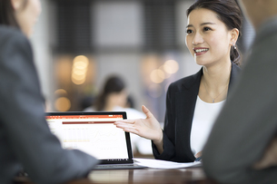テラスで商談をするビジネス女性の写真素材 [FYI04479928]