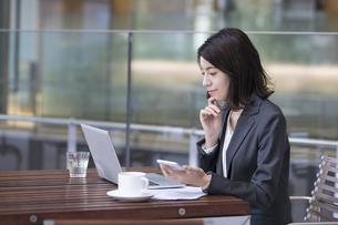 テラスでスマホを持ちパソコンを見るビジネス女性の写真素材 [FYI04479929]