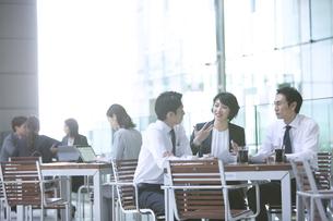 テラスで打ち合わせをする3人のビジネス男女の写真素材 [FYI04479930]