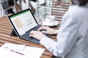 テラスでパソコンを操作するビジネス女性の手元の写真素材 [FYI04479931]