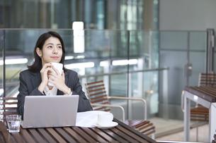 テラスでスマホを持ち遠くを見つめるビジネス女性の写真素材 [FYI04479932]