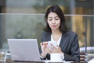 テラスでスマホを操作するビジネス女性の写真素材 [FYI04479933]