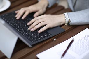 テラスでパソコンを操作するビジネス女性の手元の写真素材 [FYI04479935]