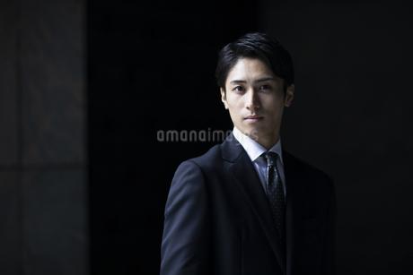 カメラ目線で立つビジネス男性の写真素材 [FYI04479936]
