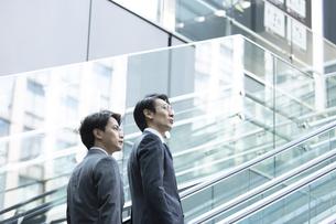 エスカレーターで上がる2人のビジネス男性の写真素材 [FYI04479939]