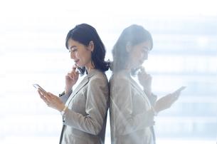 壁にもたれてスマホを見るビジネス女性の写真素材 [FYI04479948]
