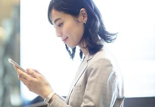 スマホを操作するビジネス女性の写真素材 [FYI04479949]