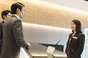 受付で対応をするビジネス女性の写真素材 [FYI04479953]