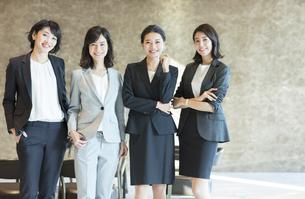 カメラ目線で立つ4人のビジネス女性の写真素材 [FYI04479960]