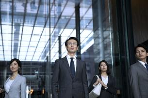 オフィスビルで遠くを見つめるビジネス男女の写真素材 [FYI04479962]