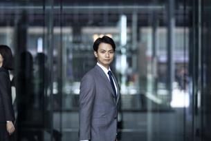 オフィスビルの前でカメラ目線で立つビジネス男性の写真素材 [FYI04479963]