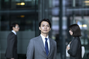 オフィスビルの前で遠くを見つめるビジネス男性の写真素材 [FYI04479964]