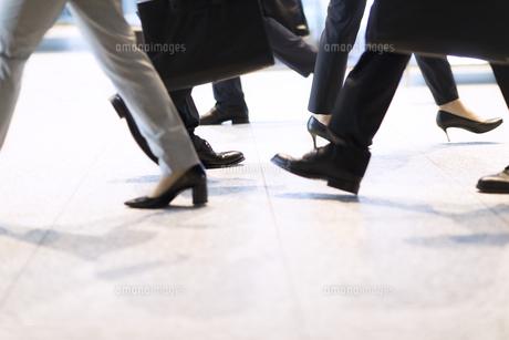 オフィスビルを歩くビジネス男女の足元の写真素材 [FYI04479968]