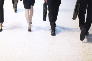 オフィスビルを歩くビジネス男女の足元の写真素材 [FYI04479971]
