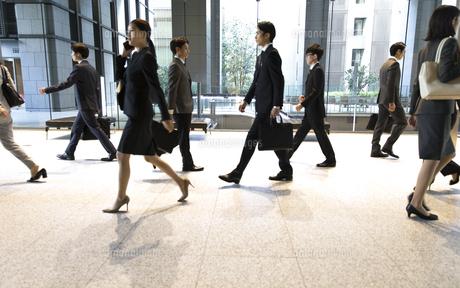 オフィスビルを歩くビジネス男女の写真素材 [FYI04479975]