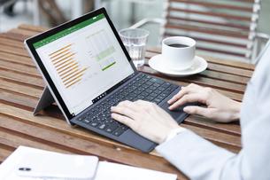 テラスでパソコンを操作するビジネス女性の手元の写真素材 [FYI04481025]
