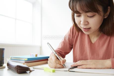 デスクで勉強をする女性の写真素材 [FYI04481028]