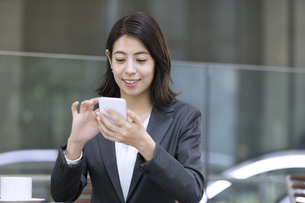 テラスでスマホを操作するビジネス女性の写真素材 [FYI04481031]