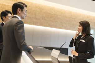 受付で対応をするビジネス女性の写真素材 [FYI04481034]