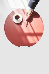 赤い丸テーブルで休憩するアイコスを持つ男性の手元の写真素材 [FYI04481036]
