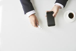 電子タバコとスマートフォンを持ったスーツの男性の手元の写真素材 [FYI04481038]
