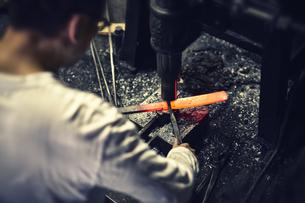 刃物工場で熱され赤くなった鉄を持ち作業する男性の写真素材 [FYI04481044]