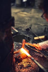 刃物工場で熱され赤くなった鉄を打つ男性の写真素材 [FYI04481051]
