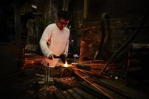 刃物工場で火花を散らしながら作業をする男性の写真素材 [FYI04481052]