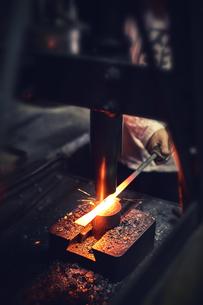 刃物工場で熱され赤くなった鉄を持ち作業する男性の写真素材 [FYI04481057]