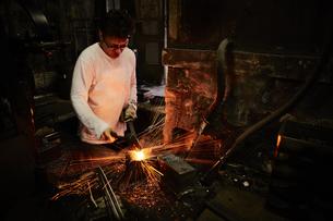 刃物工場で火花を散らしながら作業をする男性の写真素材 [FYI04481059]