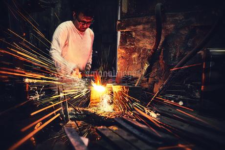 刃物工場で火花を散らしながら作業をする男性の写真素材 [FYI04481060]