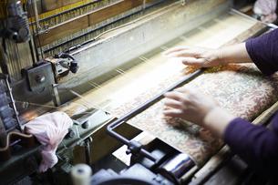 西陣織を機械に通す職人の手元の写真素材 [FYI04481071]