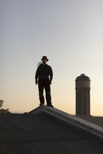 Germany, chimney sweep standing on rooftop at twilightの写真素材 [FYI04481626]