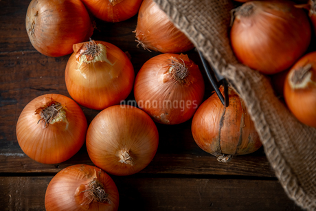 Fresh ripe onions on wood background.の写真素材 [FYI04482710]