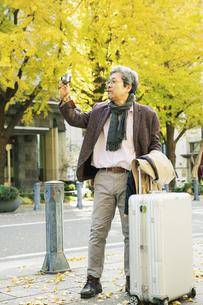 カメラを使い写真を撮る旅行中の60代男性の写真素材 [FYI04482989]