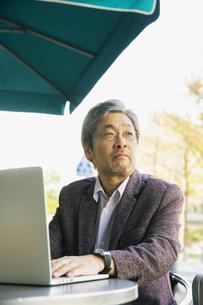 テラス席でパソコンを使う60代男性の写真素材 [FYI04483002]